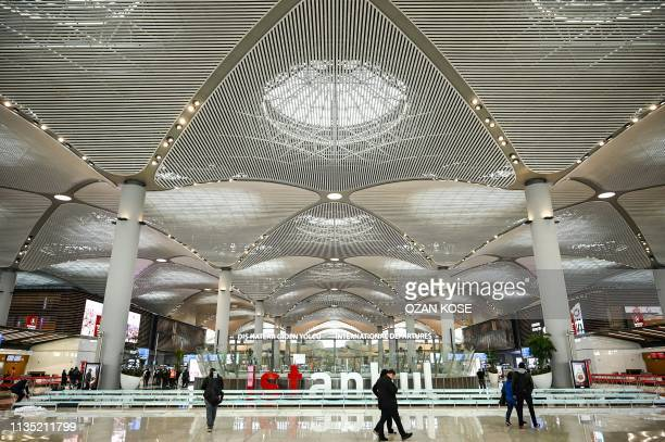 Passengers walk in the new hall of Istanbul Airport on the first day after moving from Ataturk International airport on April 6 2019 in Istanbul...