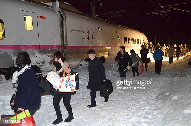 Passengers walk in the snow with Japan Railway staffs toward a replacement bus as Komachi 25 Akita Shinkansen bullet train derailment in the snow on...