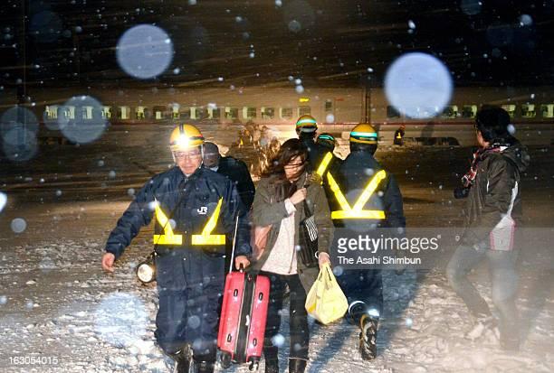 Passengers walk in the snow with Japan Railway staffs toward replacement bus as Komachi 25 Akita Shinkansen bullet train derailment in the snow on...