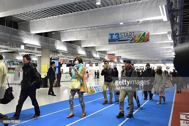 Passengers walk inside the newly opened Terminal three building of the Narita International Airport in Narita suburban Tokyo on April 8 2015 Narita...
