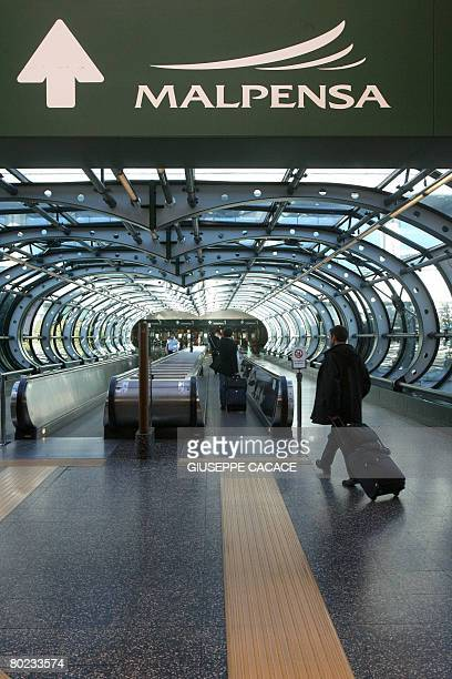 Passengers walk inside the Terminal 1 at Malpensa Airport north of Milan on March 13 2008 The province of Milan intends to propose that SEA the...
