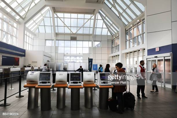 Passengers walk into the Delta terminal at LaGuardia Airport on September 26 2017 in New York City Passengers traveling through Terminal C will now...