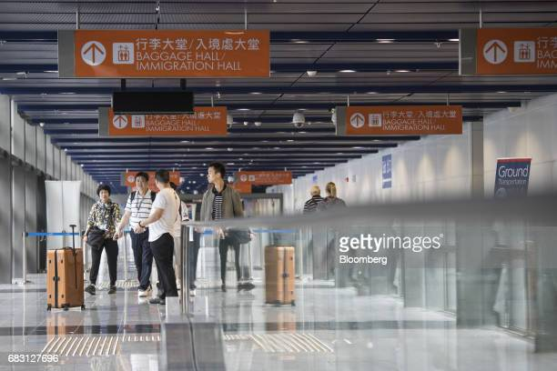 Passengers walk next to a moving walkway to board the Ovation of the Seas Quantumclass cruise ship operated by Royal Caribbean Cruises Ltd at the Kai...