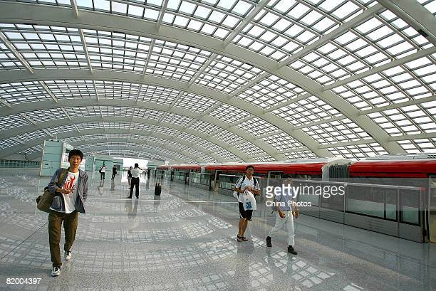 Passengers walk on the platform of the Airport Line at the Terminal 3 building of Beijing Capital International Airport on July 19 2008 in Beijing...