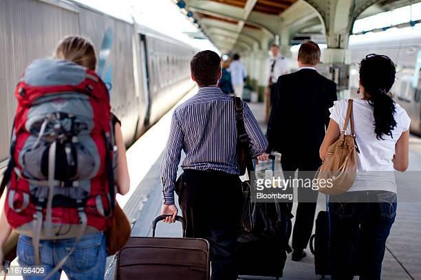 Passengers walk on the platform to board an Amtrak Acela passenger train at Union Station in Washington, D.C., U.S., on Friday, June 17, 2011. Amtrak...