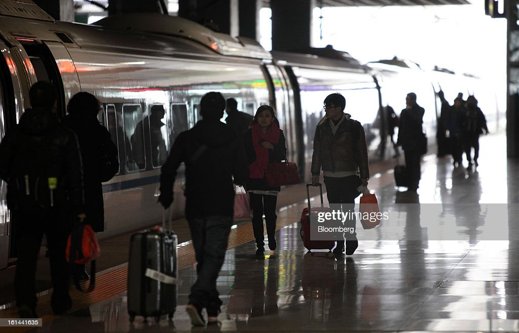 Passengers walk past a China Railways high speed train parked at Hongqiao Railway Station in Shanghai, China, on Friday, Feb. 8, 2013. A record 3.41 billion passenger trips may be made this year during the Lunar New Year period, according to the National Development and Reform Commission. Photographer: Tomohiro Ohsumi/Bloomberg via Getty Images