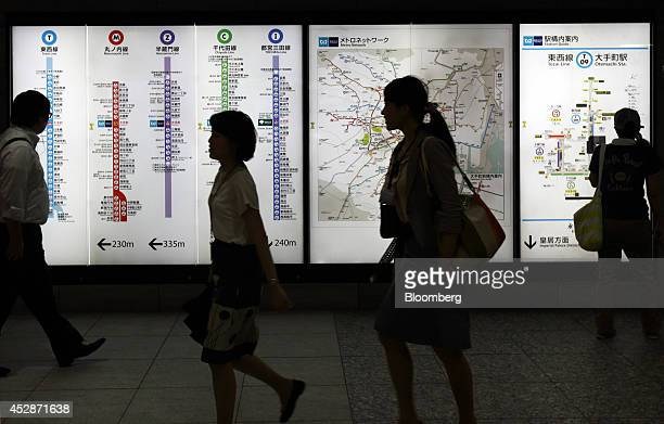 Passengers walk past a route map of subway lines in Tokyo Japan on Tuesday July 29 2014 Japan's June unemployment rate climbed 02 percent to 37...