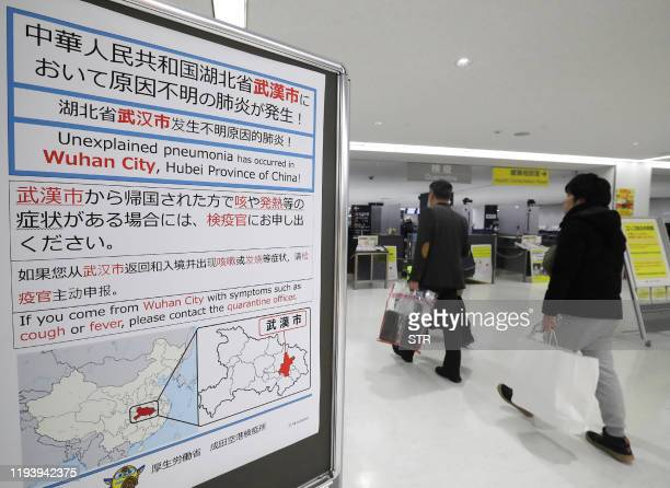 Passengers walk past a sign at Narita Airport in Chiba prefecture on January 16 2020 Japan has confirmed a case of a mystery virus that first emerged...