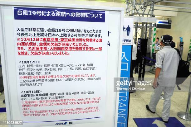 Passengers walk past a sign displaying flight cancellation following day at Itami Airport on October 11, 2019 in Toyonaka, Osaka, Japan. Massive...