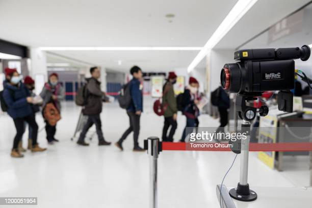 Passengers walk past a thermal scanner upon their arrival at Narita airport on January 17 2020 in Narita Japan Japan's Ministry of Health Labour and...