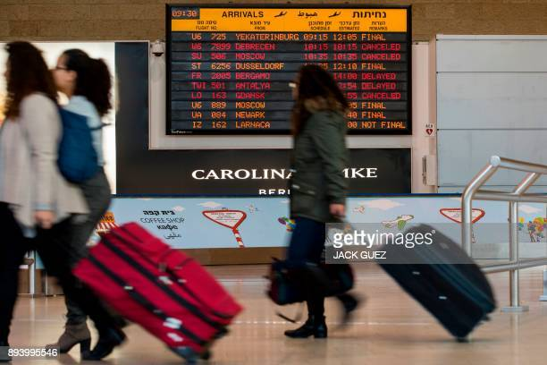 Passengers walk past an information board indicating delayed or cancelled flights during a strike at the Ben Gurion Airport near the Israeli city of...