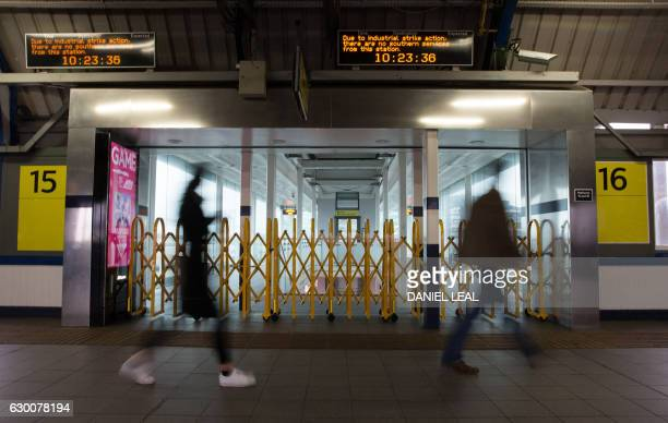 Passengers walk past barriers to platforms used by Southern Rail following strike action by staff at Clapham Junction station in London on December...
