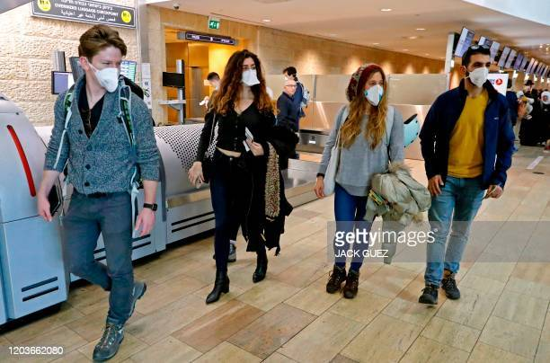 Passengers walk past check-in counters while wearing protective masks at Ben Gurion International Airport, near Tel Aviv, on February 27, 2020. -...