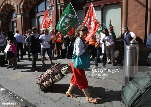 Passengers walk past pickets from the Rail Maritime and Transport Workers' Union outside Eurostar's St Pancras International terminal in central...