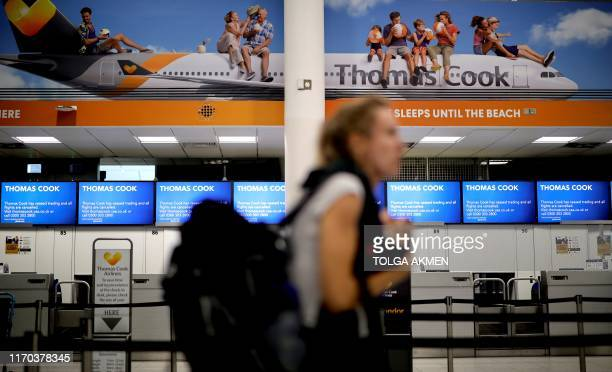 TOPSHOT Passengers walk past the closed Thomas Cook checkin desks at the South Terminal of London Gatwick Airport in Crawley south of London on...