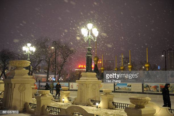 Passengers walk past the Holy Iveron Icon Orthodox Church during a heavy snowfall in Harbin China on November282017 The region's meteorological...