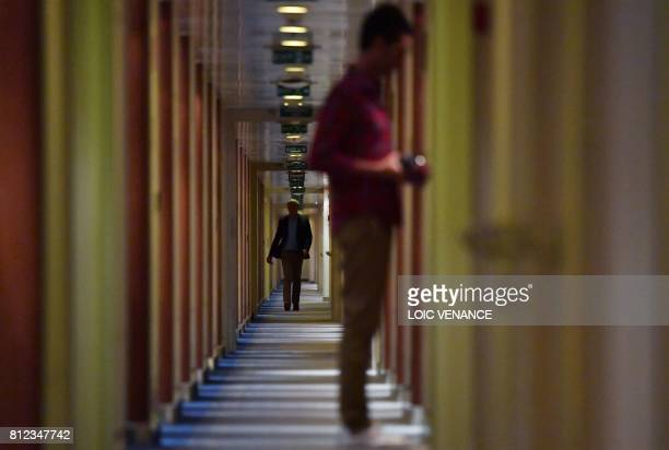 Passengers walk through a corridor of the Cunard cruise liner RMS Queen Mary 2 sailing in the Atlantic ocean during the Bridge 2017 a transatlantic...