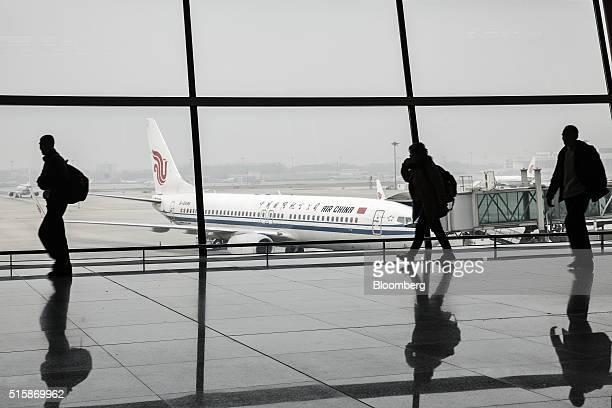 Passengers walk through a terminal building as an Air China Ltd aircraft stands on the tarmac at Beijing Capital International Airport in Beijing...