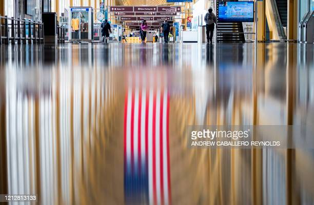 Passengers walk through an empty Ronald Reagan Washington National Airport in Arlington Virginia on May 12 2020 The airline industry has been hit...