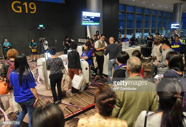 Passengers walk through automated gates at their boarding area at the newlyopened Changi International Airport's Terminal 4 in Singapore on October...