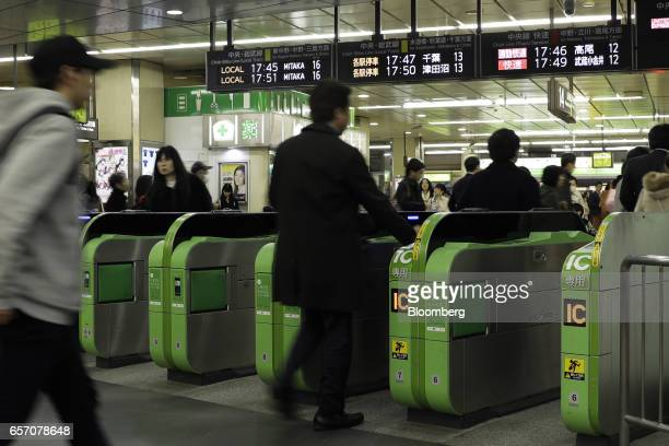Passengers walk through automatic ticket gates at East Japan Railway Co.'s Shinjuku Station in Tokyo, Japan, on Thursday, March 23, 2017. JR East,...