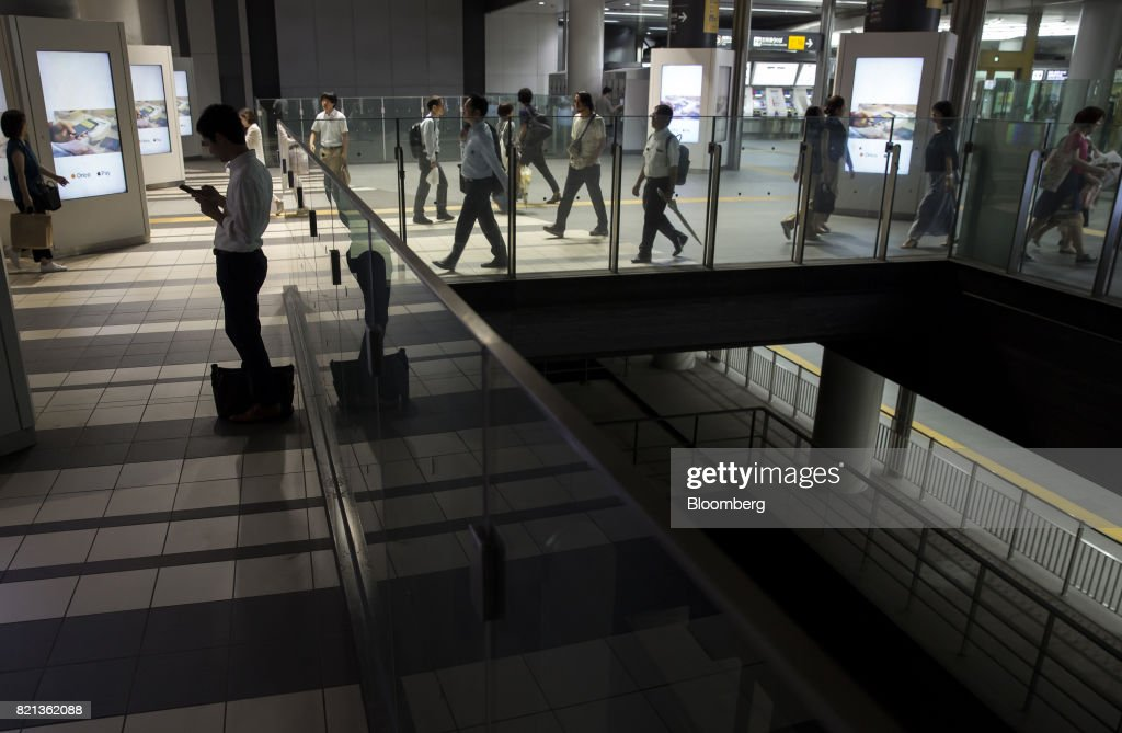 Passengers walk through Shibuya Station in Tokyo, Japan, on Tuesday, July 18, 2017. July 24 marks the first dry run of a 'Telework Day' encouraging people to work from home as the city gears up to host the 2020 Summer Olympics. Authorities are seeking ways to make room for 920,000 spectatorsexpected to visit Tokyo each day during the games. Photographer: Tomohiro Ohsumi/Bloomberg via Getty Images