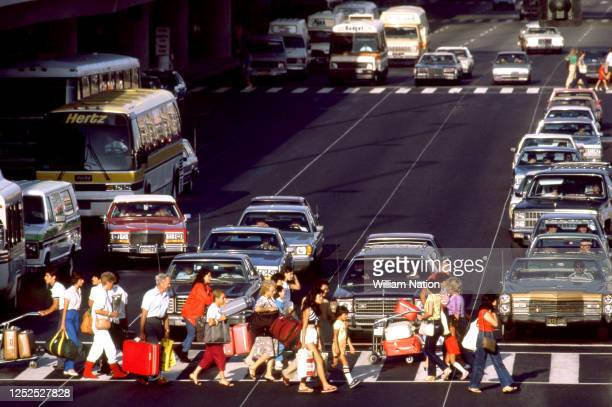 Passengers walk through the crosswalk on their way to the parking lot and the terminal circa August 1983 at the Los Angeles International Airport in...