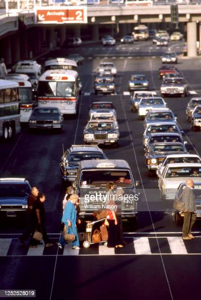 Passengers walk through the crosswalk on their way to the parking lot circa August 1983 at the Los Angeles International Airport in Los Angeles...