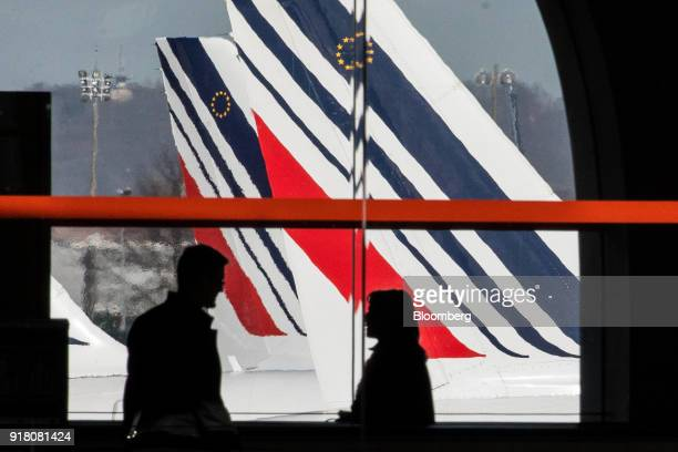 Passengers walk through the terminal as Tricolour livery sits on the tail fin of an Air France passenger aircraft beyond operated by Air FranceKLM...