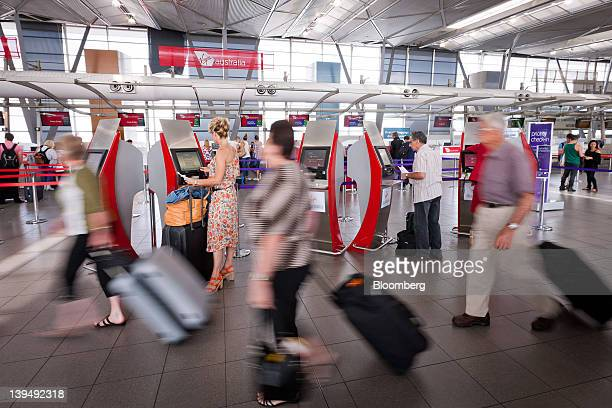Passengers walk to check in at the Virgin Australia Holdings Ltd area at the domestic terminal of Sydney airport in Sydney Australia on Wednesday Feb...