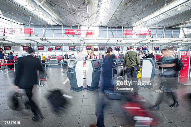 Passengers walk to checkin at Virgin Australia Holdings Ltd counters at the domestic terminal of Sydney Airport in Sydney Australia on Thursday Aug...