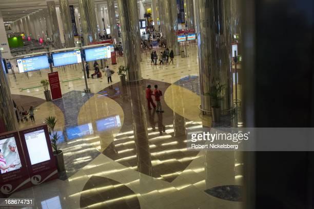 Passengers walk to the exit of Dubai International Airport terminal May 1 2013 in Dubai United Arab Emirates Dubai International Airport is the...