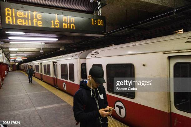 Passengers walk under a countdown clock as a Red Line train sits on the tracks at the Downtown Crossing MBTA station in Boston on Jan 18 2018 The...