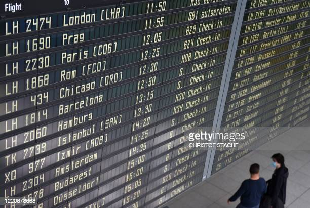 Passengers walk under a departure display in the Lufthansa terminal at the FranzJosefStrauss airport in Munich southern Germany on June 18 amid the...