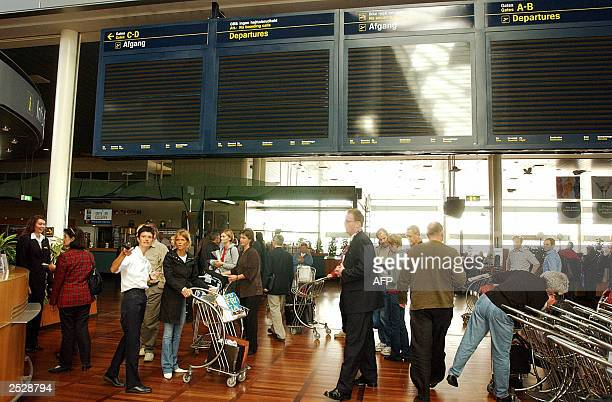 Passengers walk under blacked out information boards at Copenhagen International Airport September 23 2003 A power outage hit southern Sweden and...
