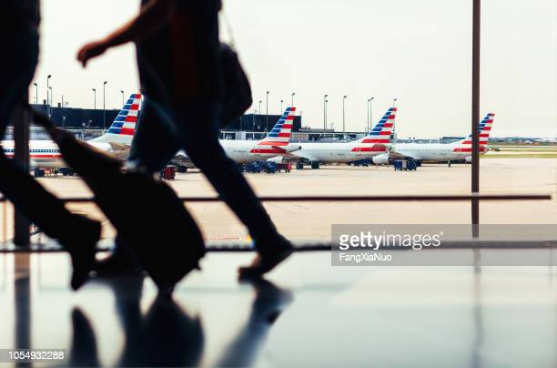 passengers walking through o'hare airport with american airlines fleet - american airlines stock pictures, royalty-free photos & images