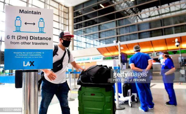 Passengers walks past thermal cameras that check passenger's body temperatures at Los Angeles International Airport in Los Angeles California on June...