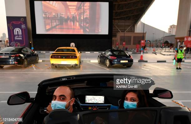 Passengers watch a movie from their car at a drivein cinema outside the Mall of Emirates in Dubai on May 17 during the COVID19 pandemic