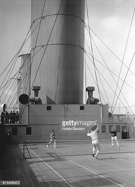 Passengers watch a tennis match played on a deck of the RMSEmpress of Britain ocean liner.