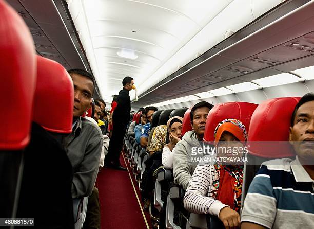 Passengers watch as an AirAsia flight attendant gives a safety demonstration while onboard a flight preparing to depart from Kuala Lumpur to Surabaya...
