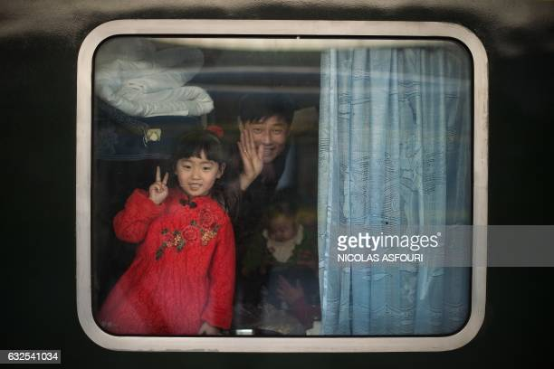 TOPSHOT Passengers wave from inside a train at the train station as they depart for their hometowns for the 'Spring Festival' or Lunar New Year on...