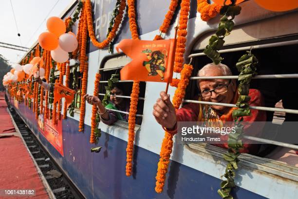 Passengers waves a flag as they sit inside the newly launched tourist train 'Ramayana Express' by Indian Railway Catering and Tourism Corporation...
