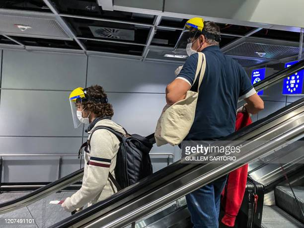 Passengers wear face masks and shields as preventive measures at the Frankfurt International Airport in Frankfurt on March 17, 2020. - Travel has...