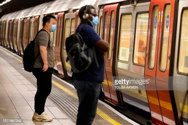Passengers wear face masks as a precaution against the transmission of the novel coronavirus as they wait on an London Underground station platform...