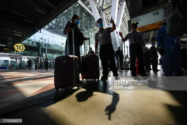 Passengers wear face masks as a protective measure against the spread of corona virus at Suvarnabhumi airport. Thailand has so far reported 2,700...