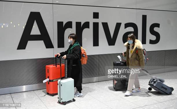 Passengers wear face masks as the push their luggage after arriving from a flight at Terminal 5 of London Heathrow Airport in west London on January...