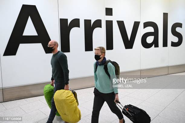 Passengers wear face masks as they arrive with their luugage at Terminal 4 of London Heathrow Airport in west London on January 28, 2020. - Chinese...
