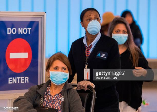 Passengers wear face masks to protect against the COVID19 after arriving at the LAX airport in Los Angeles California on March 5 2020 California has...