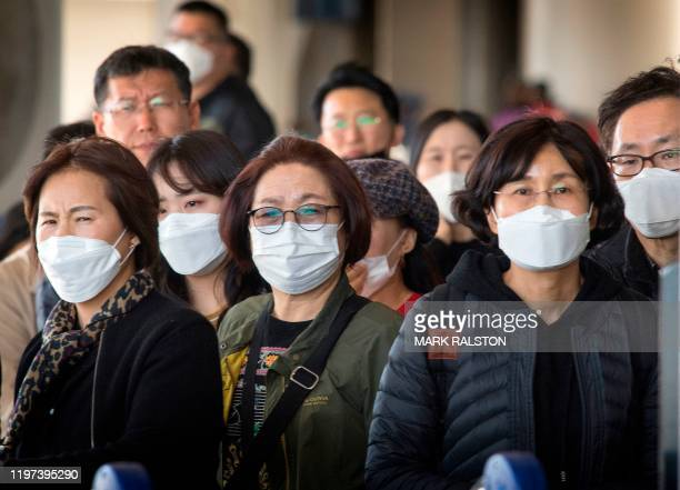 Passengers wear face masks to protect against the spread of the Coronavirus as they arrive on a flight from Asia at Los Angeles International...
