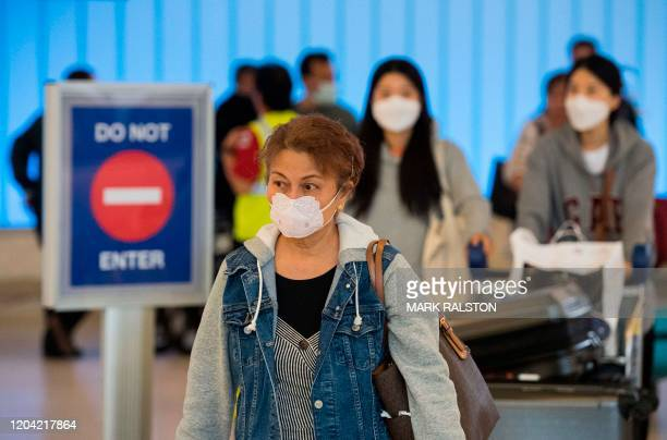 Passengers wear face masks to protect against the spread of the COVID19 coronavirus as they arrive at LAX airport in Los Angeles California on...
